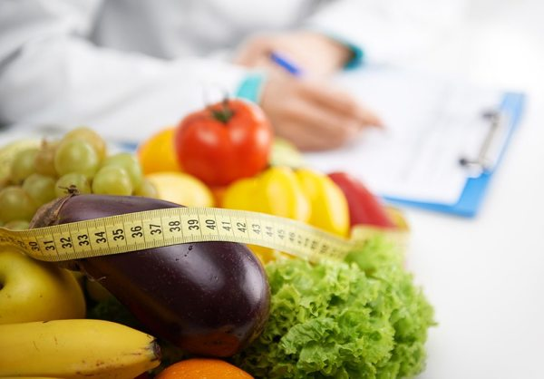 vegetables and a measuring tape in the foreground with a clinician with a clipboard in the background